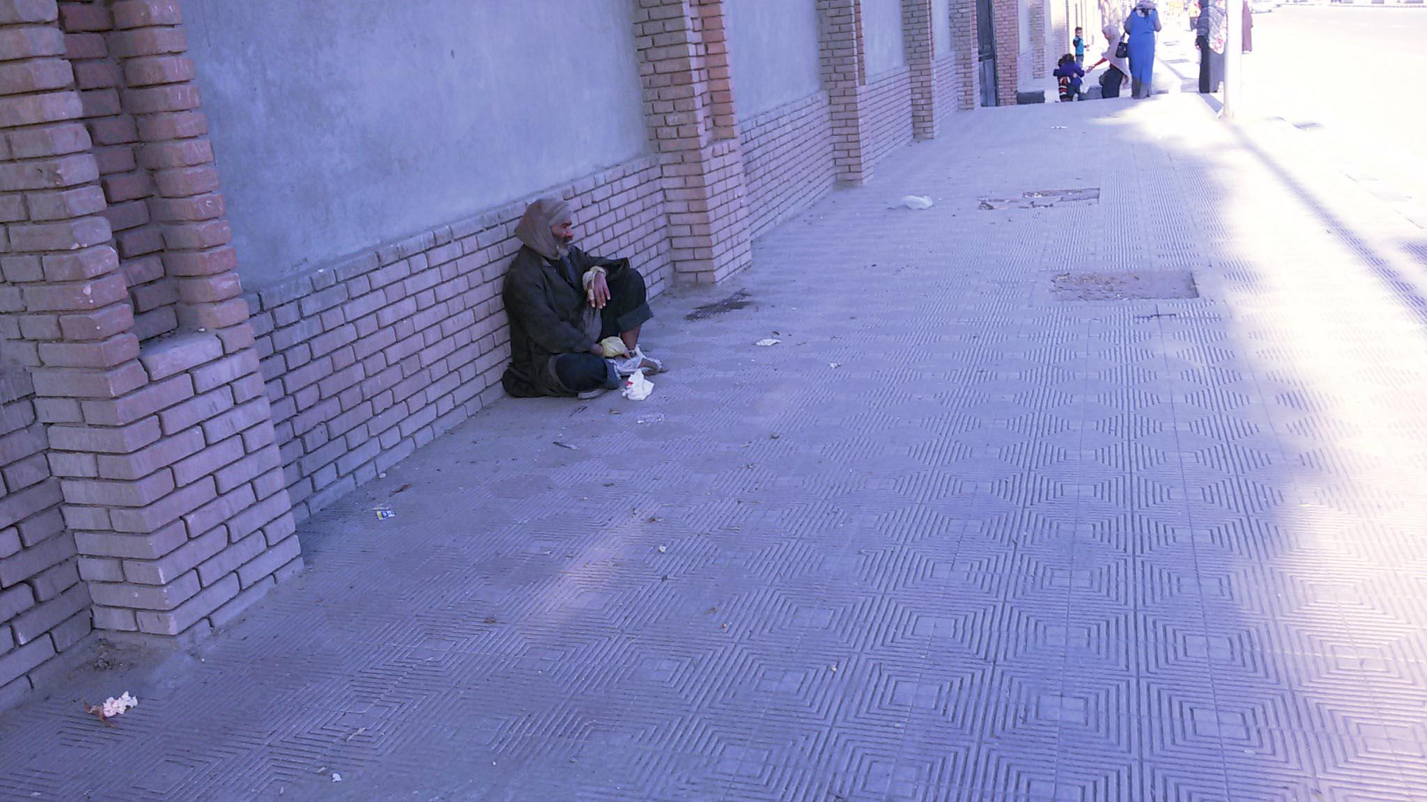 مسن يجلس على اسوار مبنى ديوان عام محافظة سوهاج المقابل لإستاد سوهاج