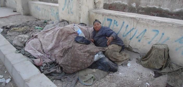خلف بيت الري بالفيوم.. عجوز تنام على الرصيف في البرد القارص (صور)