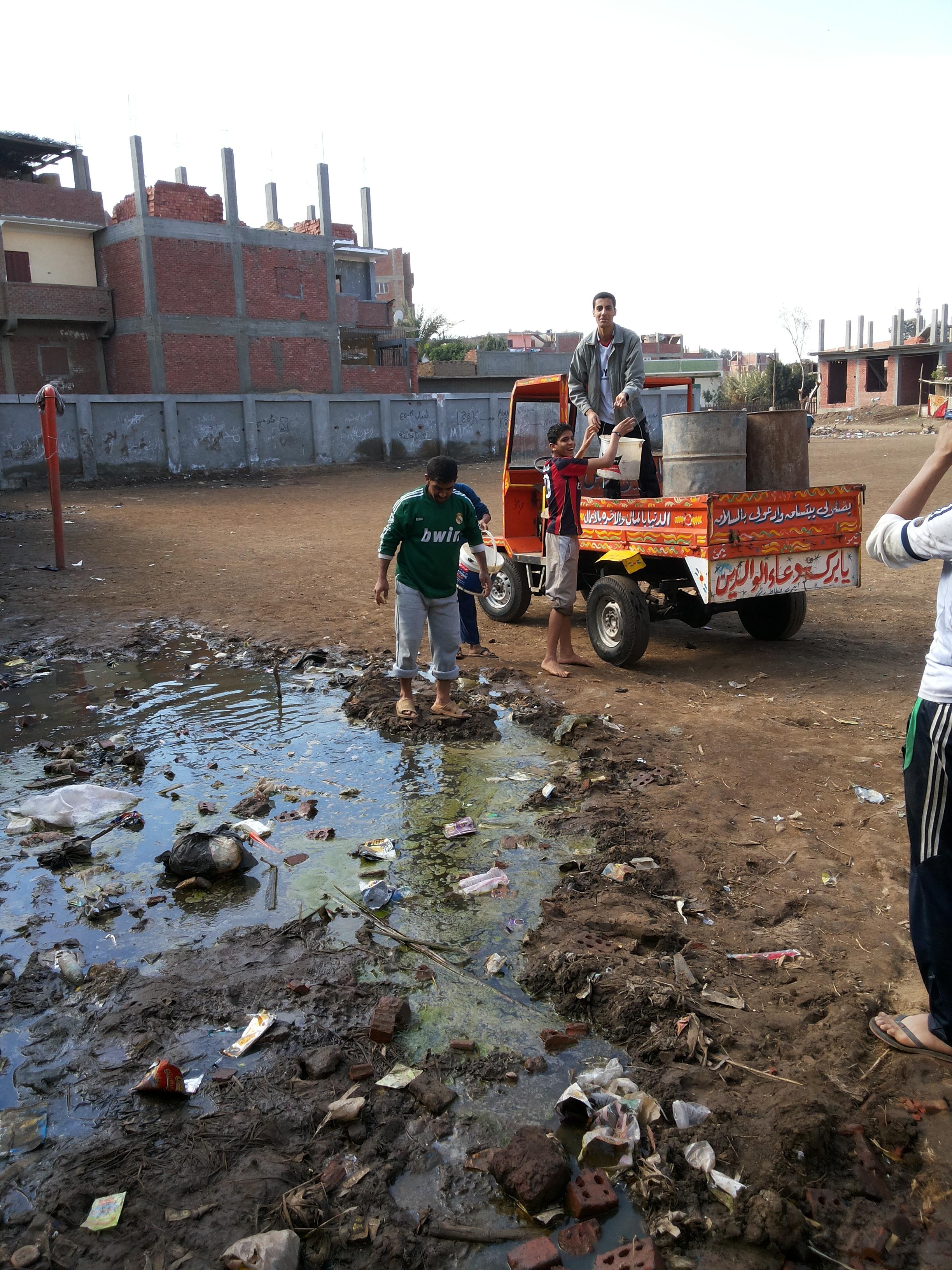 الشباب وهم ينشلون المياه المليئة بالأمراض