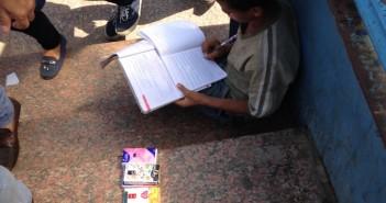 طفل يبيع المناديل ويكتب واجباته