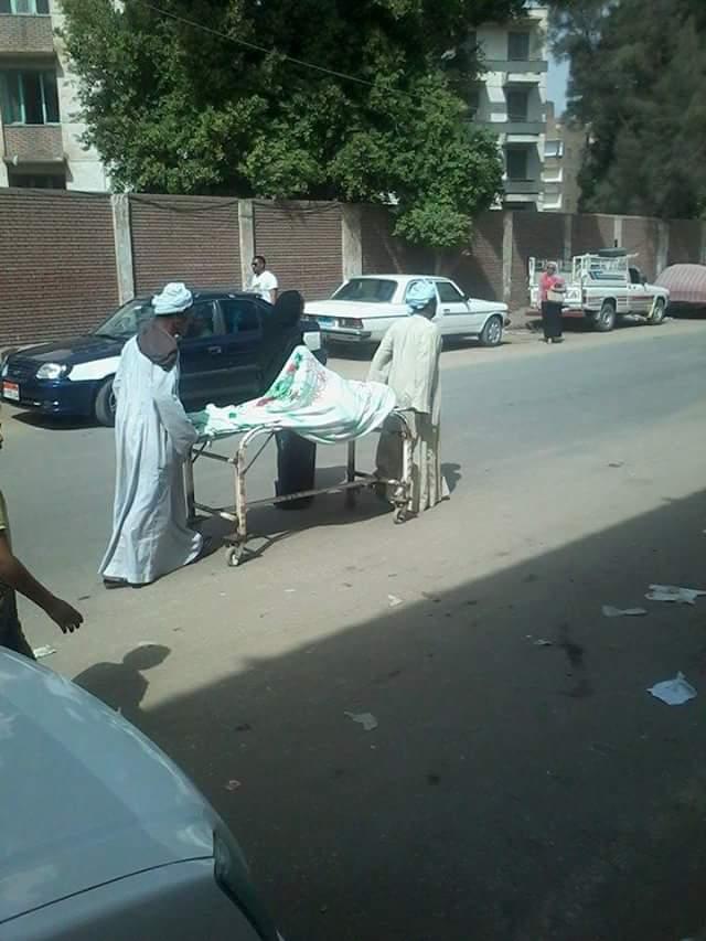 رجلان يدفعان سريرًا عليه مريضة في شارع بسوهاج