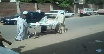 رجلان يدفعان سريرًا عليه مريضة في شارع بسوهاج بعد إغلاق المستشفى الجامعي