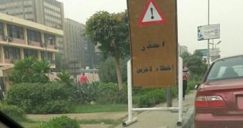 بالصورة.. لافتات مرورية كبيرة تحتل رصيف طريق النصر.. وتعرض المارة للخطر