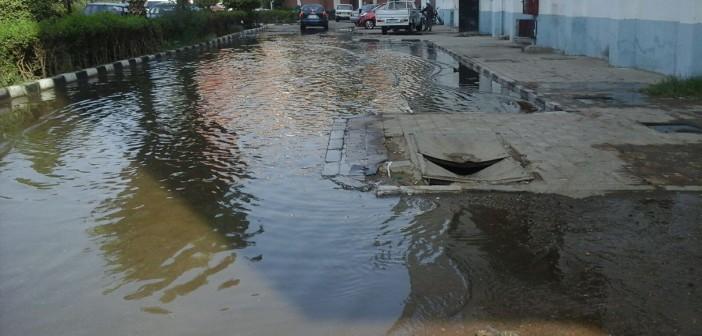 بالصور.. مياه الصرف تضرب مستشفى بأسيوط.. وصناديق المياه الغازية جسرًا لعبورها 📷