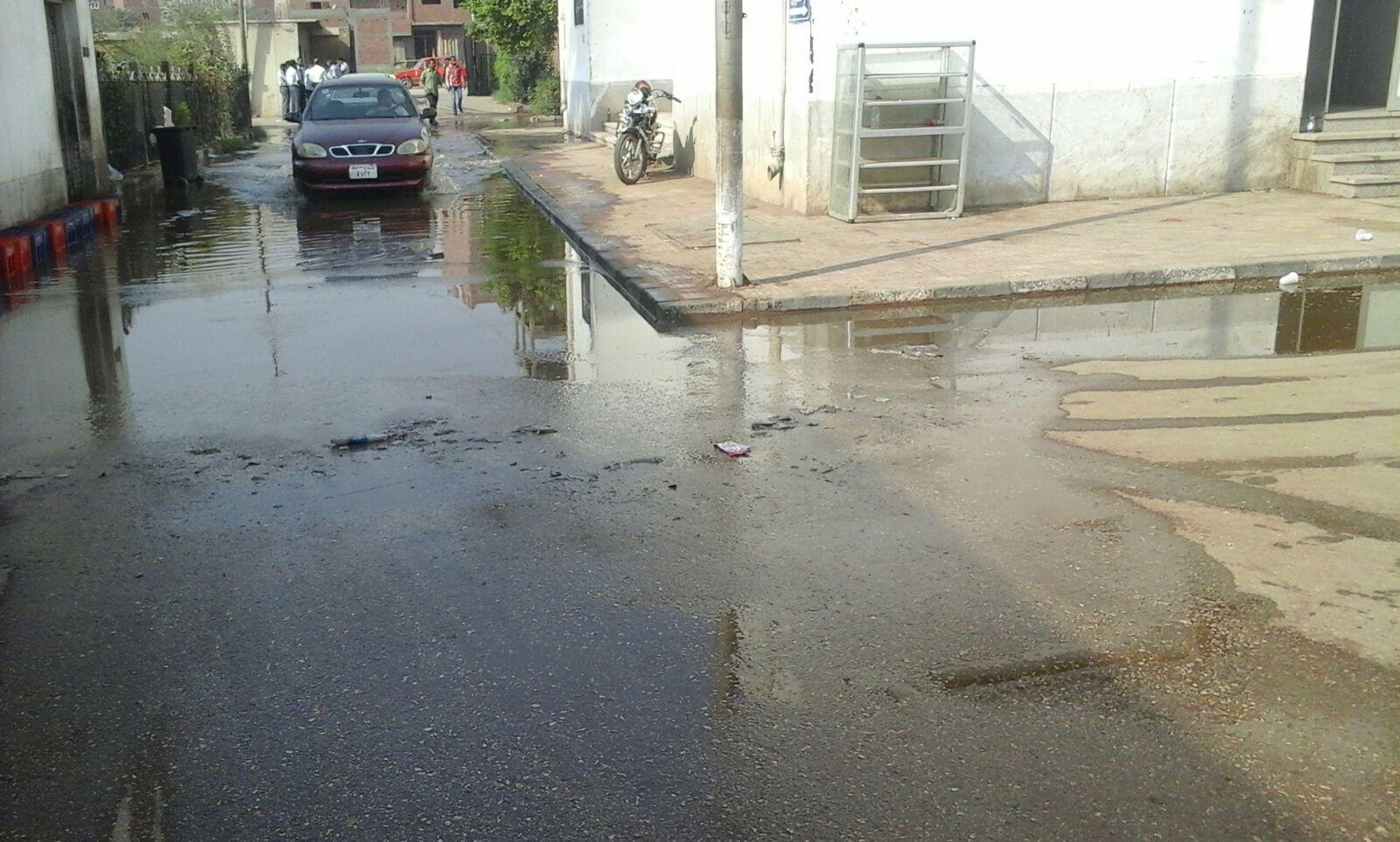 بالصور.. مياه الصرف تضرب مستشفى بأسيوط.. وصناديق المياه الغازية جسرًا لعبورها