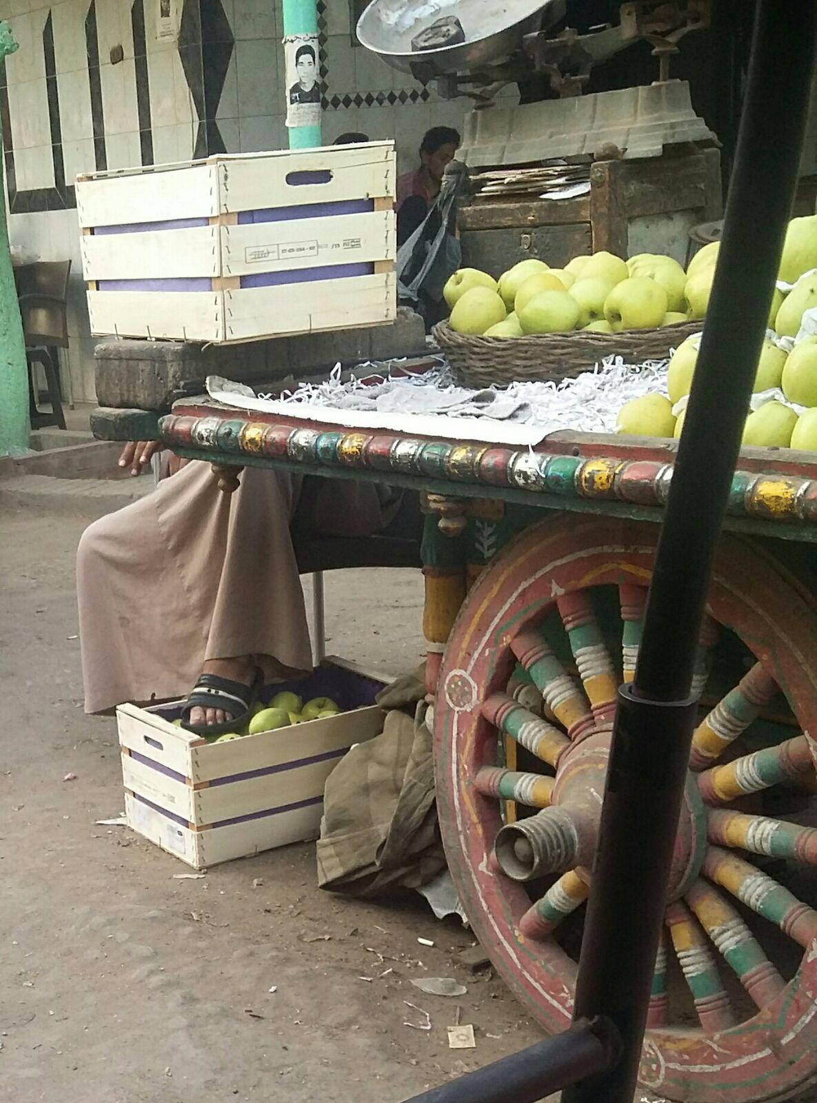 صورة.. بائع متجول يضع قدمه على ثمرات الفاكهة قبل بيعها للمواطنين
