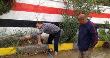 بالصور.. مدير مدرسة ومُعلم يقومان بمهمة سحب مياه الأمطار منها