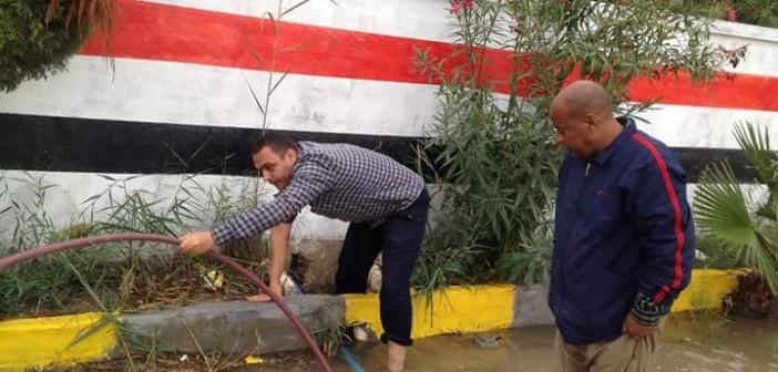 📷| بالصور.. مدير مدرسة ومُعلم يقومان بمهمة سحب مياه الأمطار منها