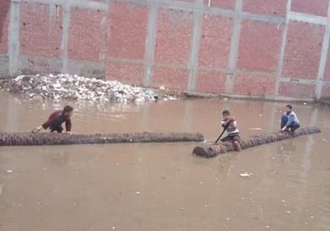 📷| في البحيرة.. مسابقة تجديف في مياه الأمطار على جذوع النخل