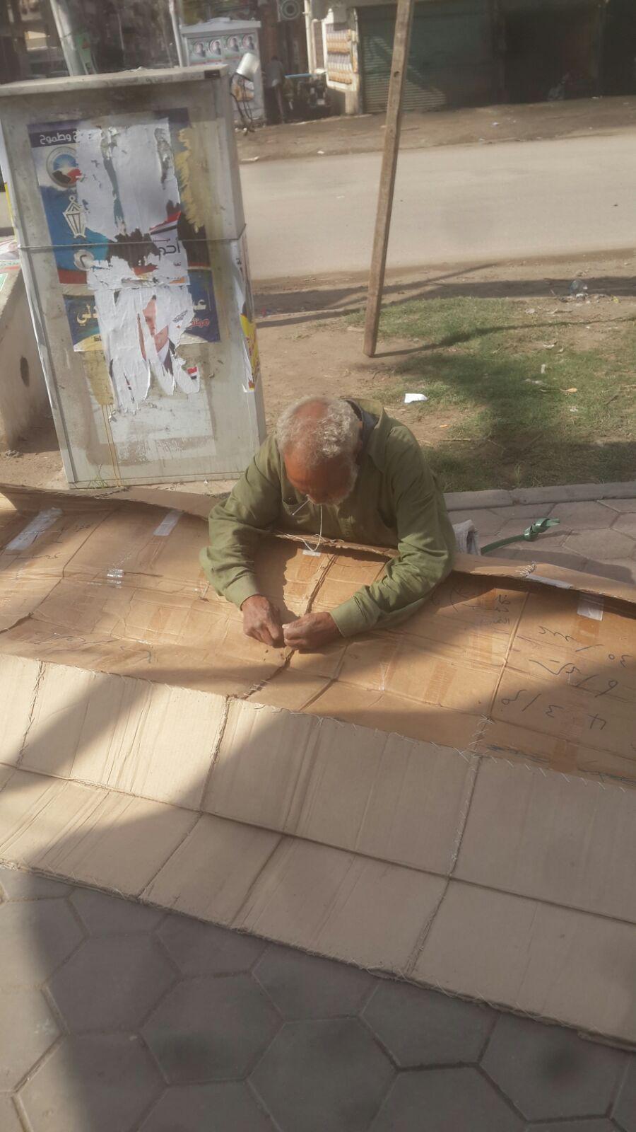 لحاف الفقر.. عجوز يخيط «الكرتون» ليقيه لسعات البرد في شوارع دمياط