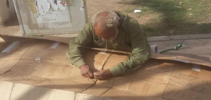 لحاف الفقر «كرتون» .. عجوز يخيط «الورق» ليقيه لسعات البرد بشوارع دمياط (صور)