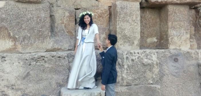 📷| عروسان من الصين يحتفلان بزواجهما والعام الجديد تحت سفح الأهرامات