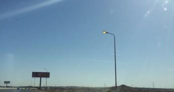 أعمدة إنارة مضاءة في وقت النهار على طريق السويس بين الرحاب ومدينتي