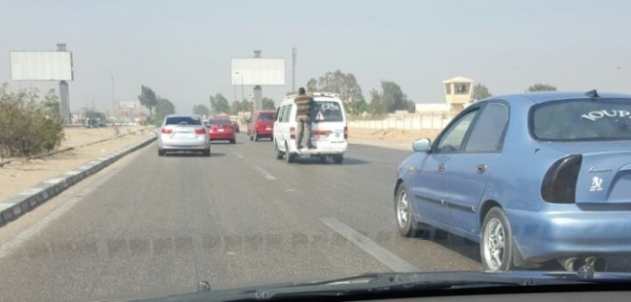 في الهوا.. راكب «متشعلق» في ميكروباص عَ الصحراوي (صور)