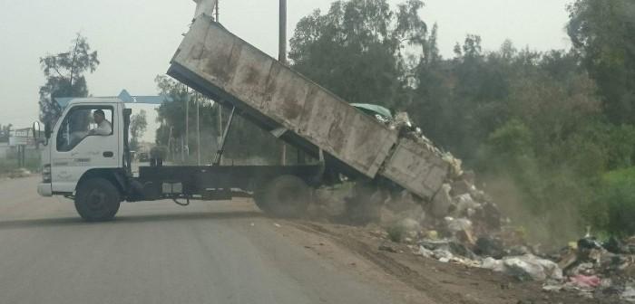 بالصور.. سيارات حكومية تتخلص من القمامة بإفراغها في إحدى قرى دمياط