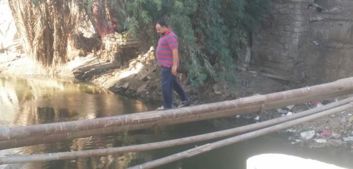 بالصور.. سكان ملوي يخاطرون بالعبور على ماسورة مياه بعد هدم كوبري رئيسي