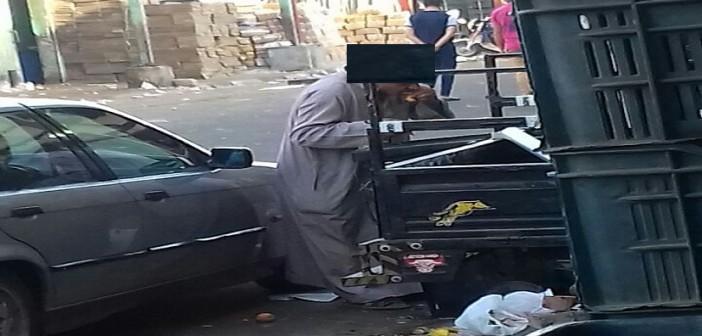 بالصور.. في سوق العبور.. عجوز يأكل مخلفات الطعام من صندوق قمامة