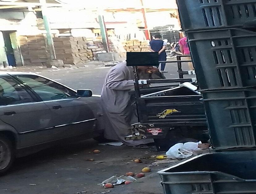 عجوز يأكل مخلفات الطعام في صندوق قمامة بسوق العبور