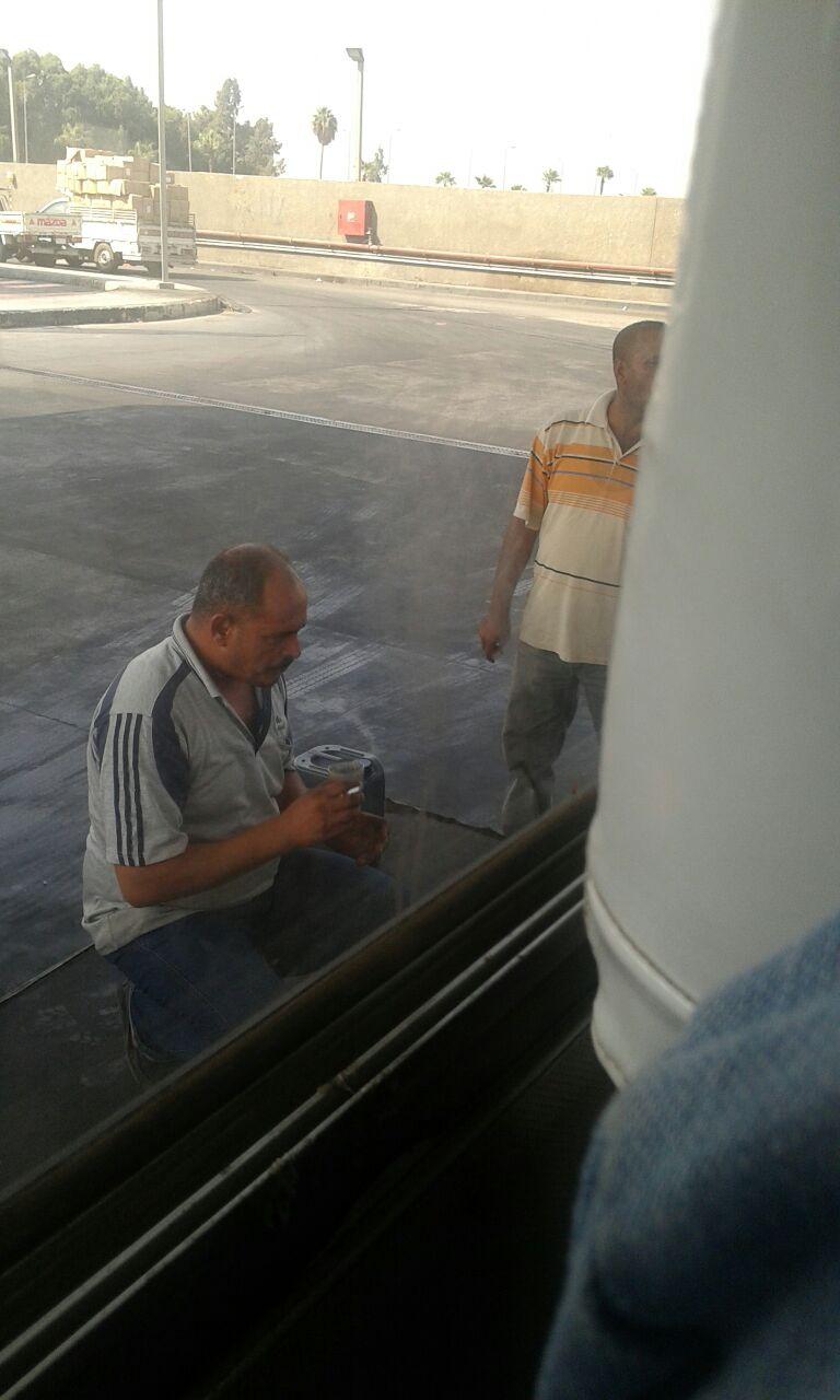 سائق يدخن السجائر أمام ماكينة ضخ البنزين بإحدى محطات الوقود (صور)