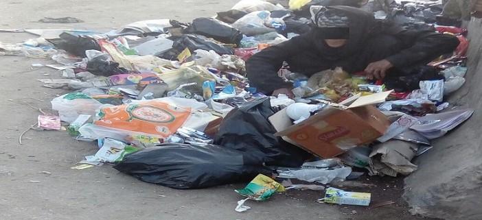 الفقر غربة في الوطن.. عجوز تنبش القمامة بحثاً عن الطعام عَ الدائري (صور)