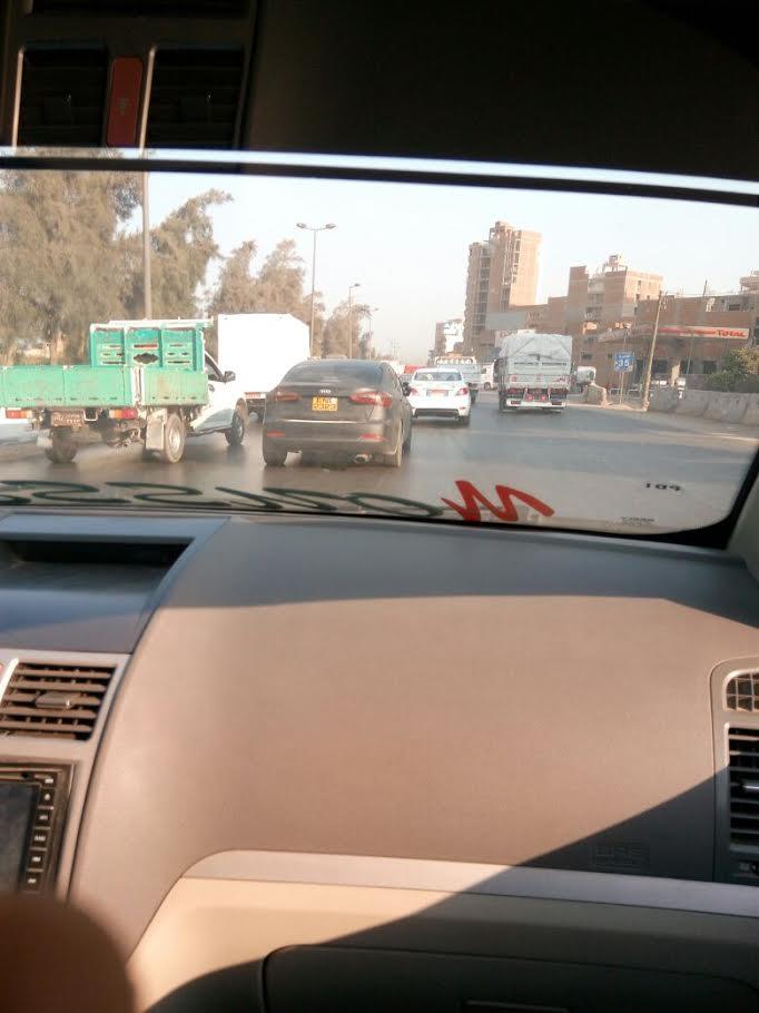سيارة بدون نمر تسير بالقرب من الطريق الدائري فى غياب رجال المرور (صور)