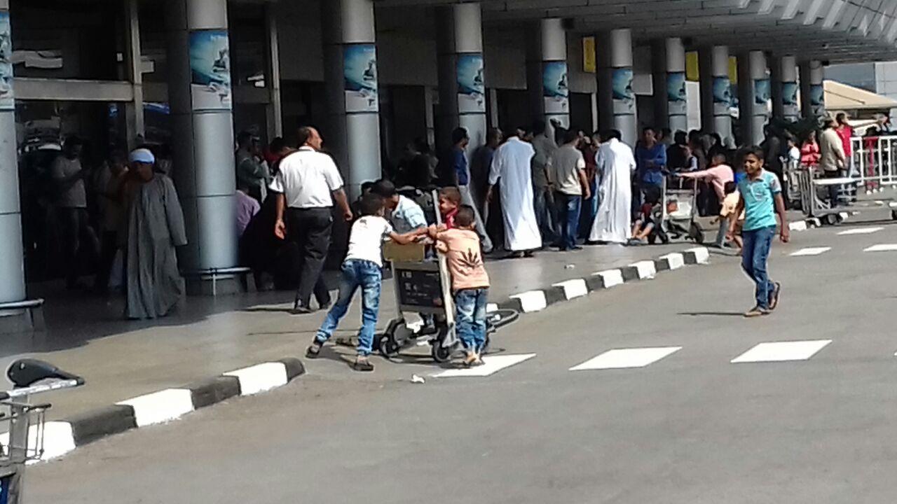 بالصور.. أطفال يلعبون بعربات حمل حقائب المسافرين بمطار القاهرة في غياب مسؤوليه