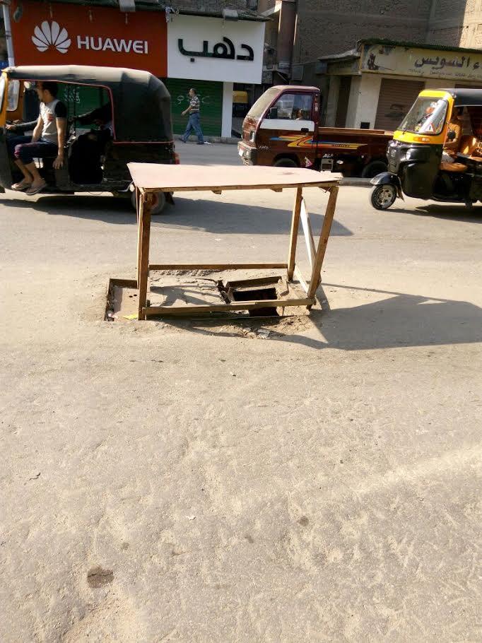 أهالي «ناهيا» يستخدمون منضدة لتغطية بلاعة مفتوحة بمنتصف الشارع (صور9