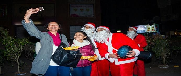 شباب يحتفلون بالكريسماس بتوزيع الهدايا على المارة في شبرا مصر (صور)