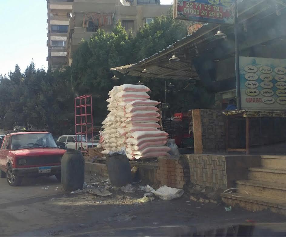 القمامة تحاصر أشولة الدقيق وضعها صاحب المخبز على الرصيف (صورة)
