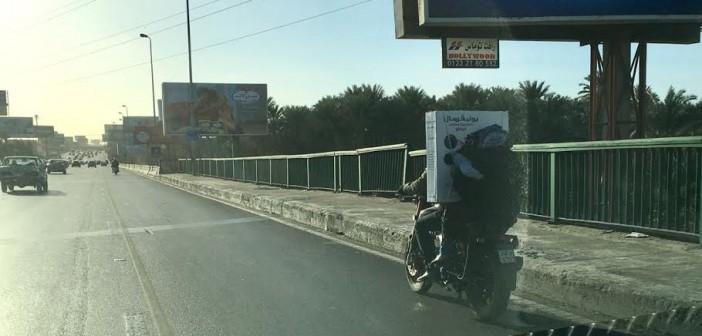طائر عَ الطريق.. مواطن يحمل زوجته وطفله وبضائع على موتوسيكل عَ المحور (صورة)