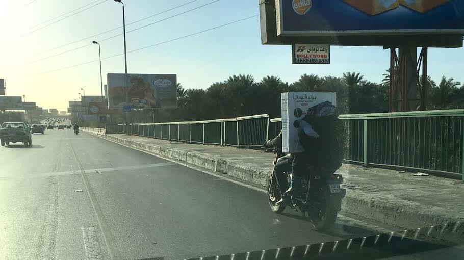 طائر على الطريق..مواطن يحمل زوجته وطفلهما وبضائع أعلى كوبر المحور (صورة)
