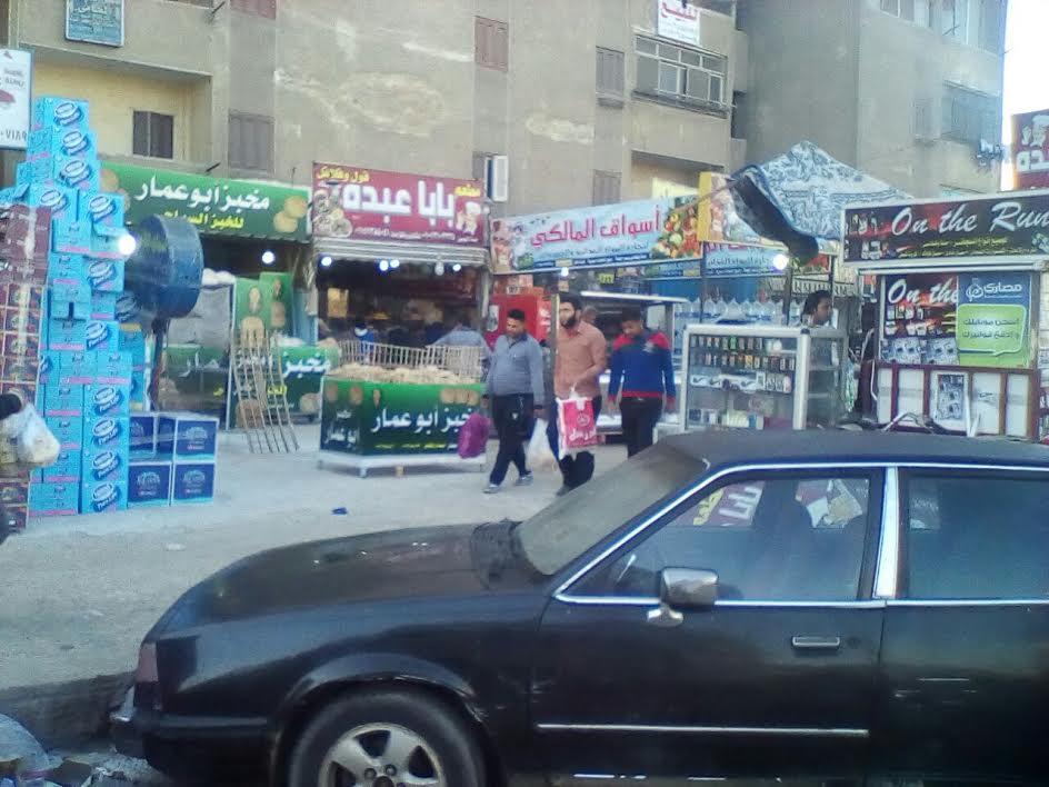 صور.. سكان «الحي العاشر» باكتوبر يشكون التعديات على الطريق من المحلات التجارية