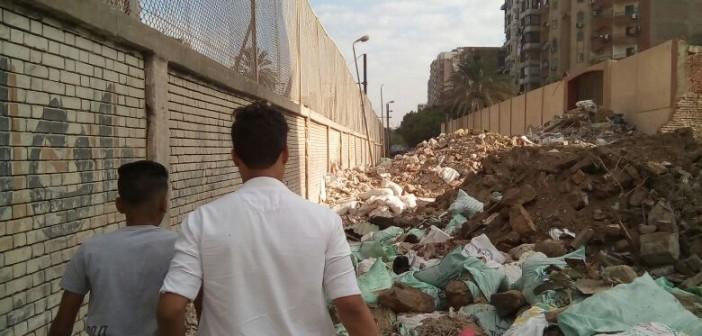 تراكم مخلفات البناء والقمامة على أسوار مدرسة بالمطرية (صور)