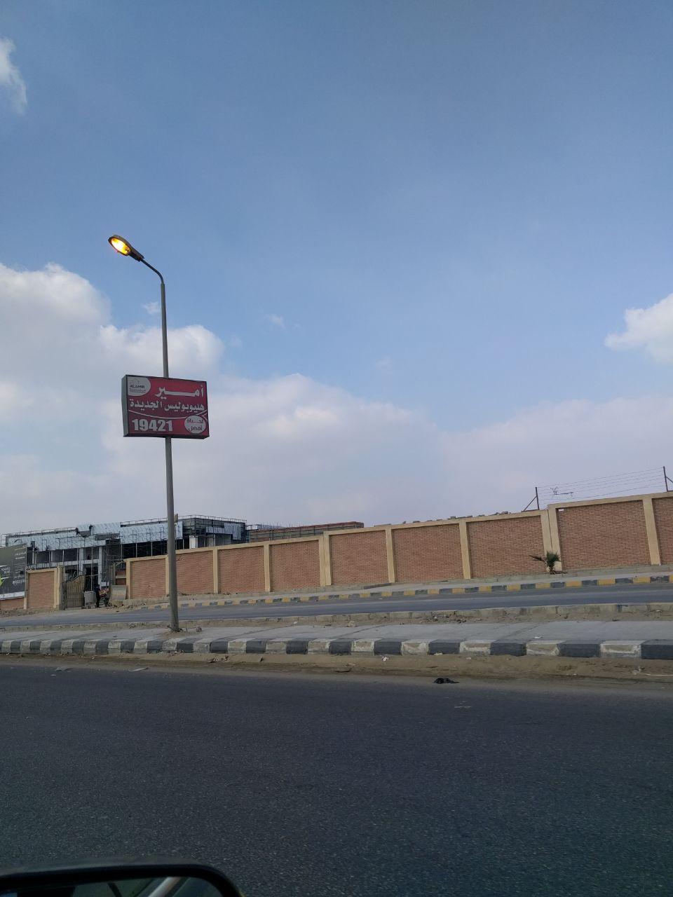 أعمدة إنارة مُضاءة نهارًا على طريق السويس في تجاه مصر الجديدة